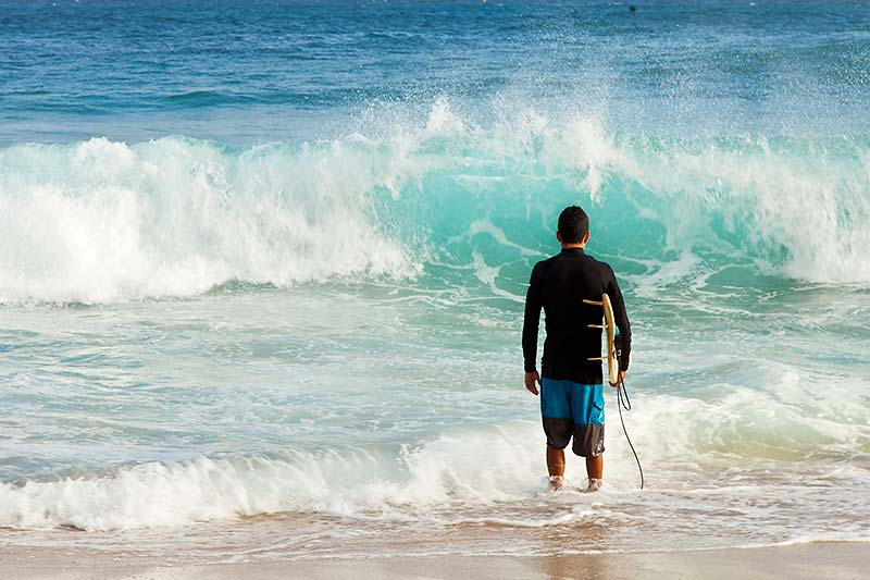 Surfer planning his entry at Shipwreck Beach, Kauai, Hawaii